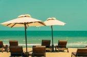 Sun loungers and umbrellas on beach — Stock Photo