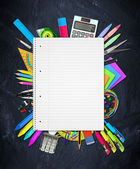 School / office supplies on blackboard — Stock Photo