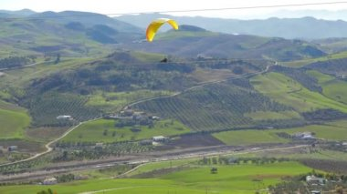 A paraglider paragliding over a green landscape — Stock Video