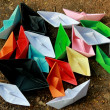 Colorful paper boats on barren land — Stock Photo #68654765