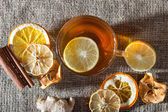 Ginger tea with spices, honey, cinnamon, lemon and dried fruit on a linen background — Stock Photo