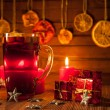 Glass of mulled wine and Christmas decorations, candles, gifts on linen background — Stock Photo #59406117