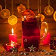 Glass of mulled wine and Christmas decorations, candles, gifts on linen background — Stock Photo #59406559