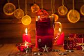 Glass of mulled wine and Christmas decorations, candles, gifts on linen background — Stock Photo