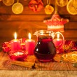Glass of mulled wine and Christmas decorations, candles, gifts on linen background — Stock Photo #59411075