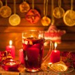 Glass of mulled wine and Christmas decorations, candles, gifts on linen background — Stock Photo #59415837