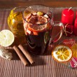 Glass of mulled wine and Christmas decorations, candles, gifts on linen background — Stock Photo #59416287