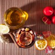 Glass of mulled wine and Christmas decorations, candles, gifts on linen background — Stock Photo #59416595