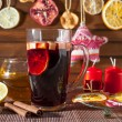 Glass of mulled wine and Christmas decorations, candles, gifts on linen background — Stock Photo #59417063