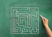Hand solving maze drawn on blackboard — Stock Photo