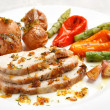 Tasty sliced roasted loin pork with potatoes, bell peppers, gooseberries and asparagus — Stock Photo #61448109