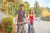 Girl and boy cycling together — Stockfoto