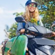 Stylish girl riding her scooter — Stock Photo #70993237