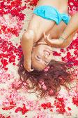 Woman lying on a flower petals — Stockfoto