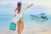Woman hitchhiking on a beach — Stock Photo