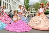 Funchal, Madeira - April 20, 2015: Performers with colorful and elaborate costumes taking part in the Parade of Flower Festival on the Madeira Island, Portugal. — Stock Photo