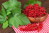 Redcurrant berry in wooden bowl — Stock Photo