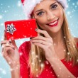 Female Santa holding a gift box — Stock Photo #59277823