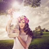 Woman with birdie in cage — Stock Photo