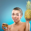 Woman choosing between pineapple and donut — Stock Photo #64598467