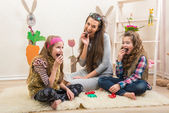 Mother and daughters eat chocolate eggs — Stock Photo