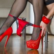 Woman in red high heels shoes is pulling panties down — Stock Photo #61282211
