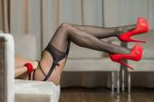 Legs with stockings, garter belt and red high heels shoes — Foto Stock