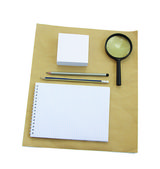 Paper notebook and magnifying glass. — Stock Photo