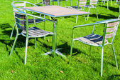 Tables and chairs in the garden at summer time — Stock Photo