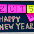 Happy New Year 2015 message hand written on blackboard, numbers stated on post-it notes, 2015 replacing 2014, corporate office celebration concept — Stock Photo #56986003