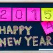 Happy New Year 2015 message hand written on blackboard, numbers stated on post-it notes, 2015 replacing 2014, corporate office celebration concept — Stock Photo #56986347