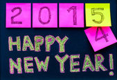 Happy New Year 2015 message hand written on blackboard, numbers stated on post-it notes, 2015 replacing 2014, corporate office celebration concept — Stock Photo