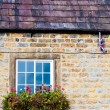 Architecture detail of traditional English cottage, with pots of flowers at the window and British flag on the wall — Stock Photo #57560975