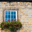 Architecture detail of traditional English cottage, with pots of flowers at the window and British flag on the wall — Stock Photo #57561037