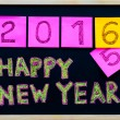 Happy New Year 2016 message hand written on blackboard, numbers stated on post-it notes, 2016 replacing 2015, corporate office celebration concept — Stock Photo #58599491