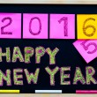 Happy New Year 2016 message hand written on blackboard, numbers stated on post-it notes, 2016 replacing 2015, corporate office celebration concept — Stock Photo #58599505