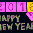 Happy New Year 2016 message hand written on blackboard, numbers stated on post-it notes, 2016 replacing 2015, corporate office celebration concept — Stock Photo #58600093