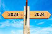Wooden signpost with two opposite arrows over clear blue sky, year 2023 and 2024 signs, Happy New Year conceptual image — Stock Photo