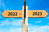 Wooden signpost with two opposite arrows over clear blue sky, year 2022 and 2023 signs, Happy New Year conceptual image — Stock Photo