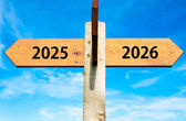 Wooden signpost with two opposite arrows over clear blue sky, year 2025 and 2026 signs, Happy New Year conceptual image — Stock Photo