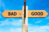 Wooden signpost with two opposite arrows over clear blue sky, Bad and Good signs, Choice conceptual image — Stock Photo