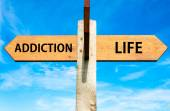 Wooden signpost with two opposite arrows over clear blue sky, Addiction and Life signs, Choice conceptual image — Stock Photo
