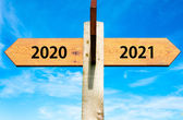 Wooden signpost with two opposite arrows over clear blue sky, year 2020 and 2021 signs, Happy New Year conceptual image — Stock Photo
