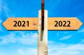 Wooden signpost with two opposite arrows over clear blue sky, year 2021 and 2022 signs, Happy New Year conceptual image — Stock Photo