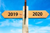 Wooden signpost with two opposite arrows over clear blue sky, year 2019 and 2020 signs, Happy New Year conceptual image — Stock Photo