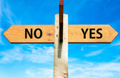 Wooden signpost with two opposite arrows over clear blue sky, YES and No messages, Decisional conceptual image — Stock Photo