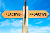 Wooden signpost with two opposite arrows over clear blue sky, Reactive versus Proactive messages, Behaviour conceptual image — Stock Photo