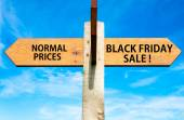 Wooden signpost with two opposite arrows over clear blue sky, Normal Prices versus Black Friday sale messages, Sales conceptual image — Stock Photo