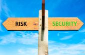 Wooden signpost with two opposite arrows over clear blue sky, Risk versus Security messages, Lifestyle change conceptual image — Stock Photo
