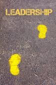 Yellow footsteps on sidewalk towards Leadership message — Stock Photo